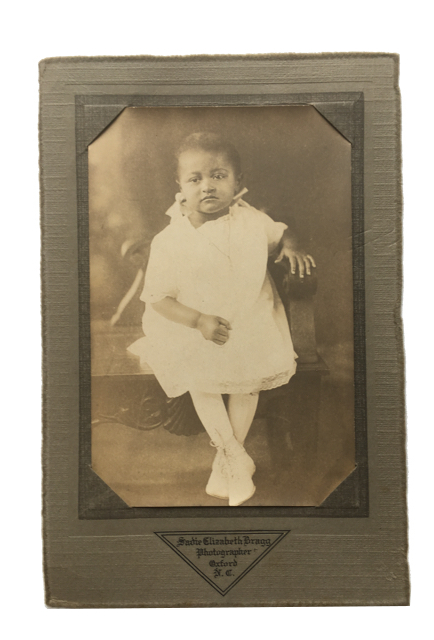 Unsmiling young African American Girl. Photograph.